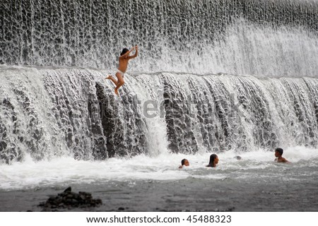 BALI - JANUARY 16: Children jump off the spillway and enjoy a morning swim at the dam in Ubud  January 16, 2010 in Bali, Indonesia.