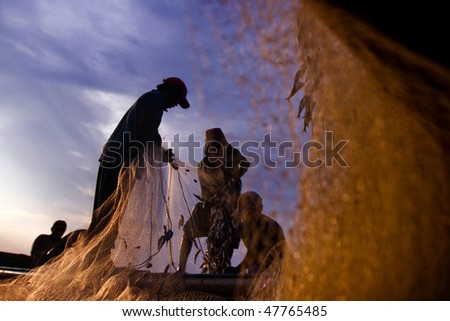 BALI - JANUARY 16: Life in a fishing village, fishermen repair nets at dusk at Jimbaran village, Bali January 16, 2010 in Bali, Indonesia.