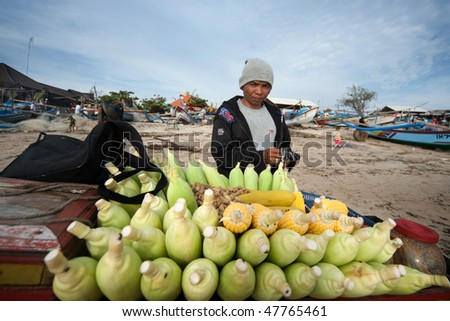 BALI - JANUARY 16: Life in a fishing village, trader sells steamed corn on the beach at Jimbaran village, Bali January 16, 2010 in Bali, Indonesia.