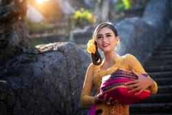 Bali Lady in Traditional dress walk in old temple, indonesia