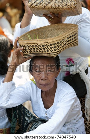 BALI - OCTOBER 30: The elderly woman in national clothes with a gift to Gods on celebrating of Day of the Temple on October 30, 2009 in Bali, Indonesia