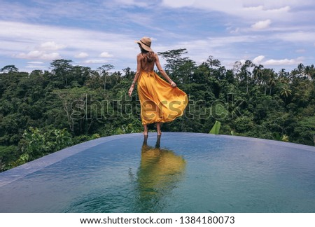 Bali travel series. photo of beautiful woman with dark hair in elegant yellow dress posing on the edge of the pool with jungle view