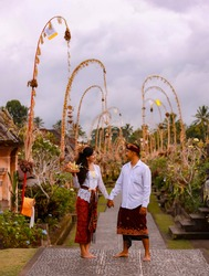 Balinese ceremony. Multicultural couple going to Hindu religious ceremony with god's offerings. Penjor bamboo decoration. Caucasian wife and Balinese husband. Penglipuran village, Bali, Indonesia