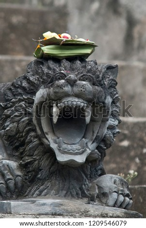 Balinese feline statue with typical offering on his head #1209546079