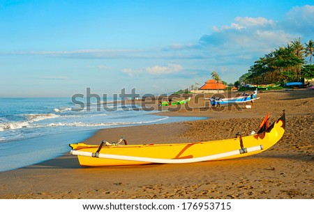 Balinese fisherman village at sunrise. Traditional Balinese fisherman boat on foreground - stock photo