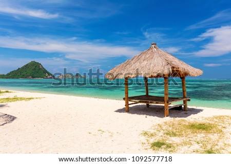 Balinese hut on the white sandy Kuta Beach, Lombok, Indoneasia - Shutterstock ID 1092577718