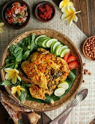Balinese Indonesian food, Ayam Betutu.  Whole chicken filled with Balinese seasoning cassava leaves, wrapped in banana leaves and steamed.  Served with Sambal Matah and Roasted Peanuts.