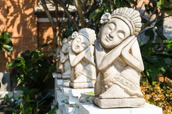 Balinese sculpture in tropical garden, outdoor day light, traditional Bali style sculpture