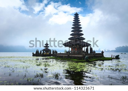 Balinese temple situated in a lake among mountains - stock photo