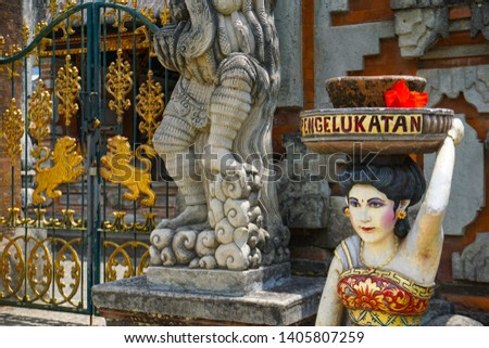 Balinese woman statue holding on his head offerings and gifts to the gods at the Balinese Temple, Bali, Indonesia.