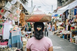 Balinese women carrying something on her head and walking in Ubud market of Bali, Indonesia.