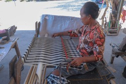 Balinese women work in an open weaving workshop on looms. Processing of hand-dyed cotton fibers. Workers work in a loom house and create fabrics with bright patterns. Bali, Indonesia.