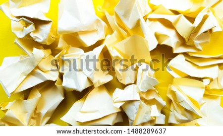 Ball crumpled paper ball isolated on a yellow background. Crumpled paper for texture. Crumpled paper after a brainstorming was thrown into the bin. A piece of yellow crumpled paper on a yellow #1488289637