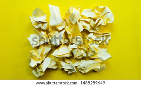 Ball crumpled paper ball isolated on a yellow background. Crumpled paper for texture. Crumpled paper after a brainstorming was thrown into the bin. A piece of yellow crumpled paper on a yellow #1488289649