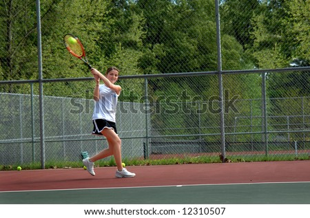 Ball is hit by tennis player.  Female teen runs to return volley during game.