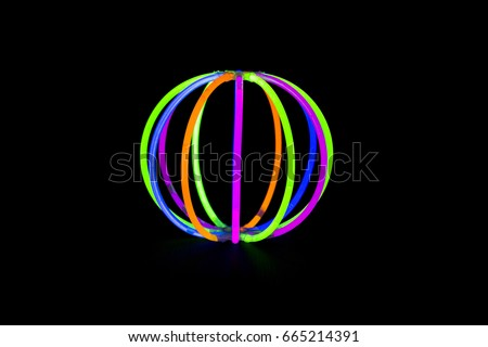 Ball made with glow sticks neon light fluorescent on back background. variation of different colored chem lights like a ball #665214391