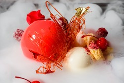Ball mousse cake, yogurt spheres, cherries, raspberries and a caramel decoration in steaming dry ice, close-up. Molecular gastronomy dessert.