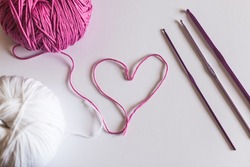 Ball of cotton forming a heart and purple crochet needles with white background