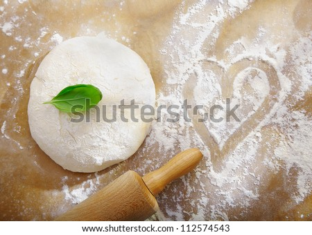 Ball of fresh dough left to rise alonside a scattering of flour with a handdrawn heart symbolic of preparing dinner for a date with love