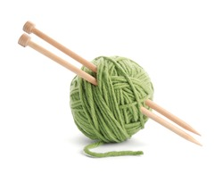 Ball of thread and knitting needles on white background