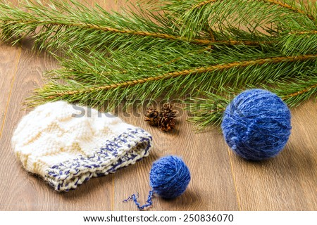 ball of threads, knitting cap, pine-cones and branch of  pine on wooden background