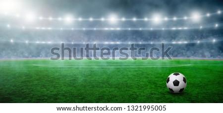 Ball on gras in soccer stadium with illumination at night