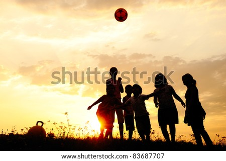 Ball playing group of happy children on meadow, sunset, summertime