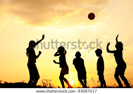 Ball playing  happy children playing on meadow, sunset, summertime
