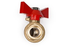 Ball valve with brass body and red butterfly handle on a white background, view of the pivoting ball of partly open valve from threaded connection side close-up in selective focus