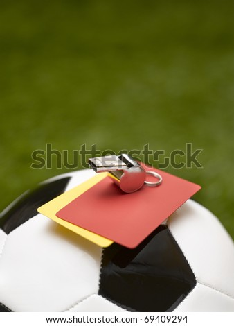 ball, whistle and warning cards in soccer field
