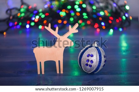 Ball with ornaments and wooden deer toy on blurred colorful garland background. Christmas decor. Symbols of winter holiday christmas. Deer and toy decorative ornament. Merry Christmas concept. #1269007915