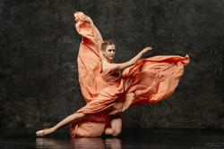 Ballerina. A young ballet dancer dressed in a long peach dress, pointe shoes with ribbons. The girl performs an elegant, graceful dance movement. Beautiful classic ballet. Advertising ballet school.