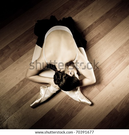 Ballerina dancer sitting down with her legs crossed on the wooden floor