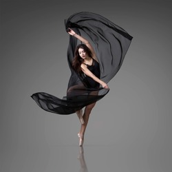 Ballerina dances with a black flying cloth. Color photo.