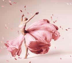 ballerina dancing in flowing pink dress with flying petals in studio