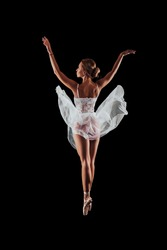 ballerina dancing in studio on a black background. dancer in motion with his back. isolated. young ballet dancer