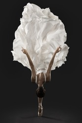 Ballerina Graceful Jump in White Silk Dress, Ballet Dancer Pointe Shoes in Fluttering Cloth, Black Background