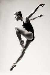 ballerina in a black swimsuit on a white background