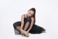 Ballerina in a black transparent tutu sitting on the floor. Tired girl looking down. Dancer touching her foot isolated on white background