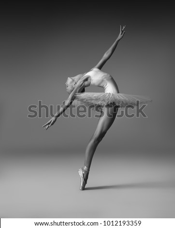 Ballerina in a tutu and pointe shoes makes a beautiful pose.  Black and white photo.