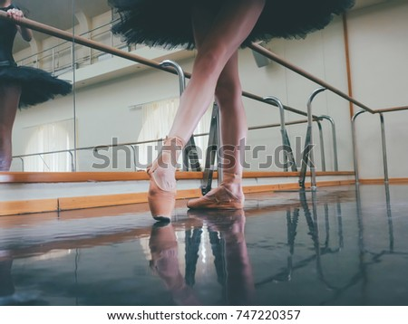 Ballerina in ballet pointe stretches on barre in gym. Woman practicing in dance studio. Work out of young girl.