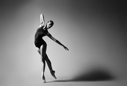 Ballerina in black outfit posing on toes, studio background. Grayscale image.