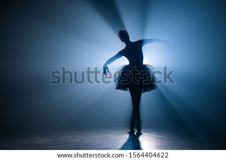 Ballerina in black tutu dress dancing on stage with magic blue light and smoke. Silhouette of young attractive dancer in ballet shoes pointe performing in dark. Copy space. Foto stock ©