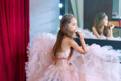 Ballerina little cute girl wear pink dress sitting on a chair in the dressing room and make yourself a makeover. She holding brush in her hand for applying makeup with reflection in mirror.