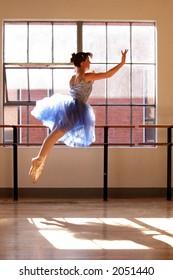 A stock photo of a ballerina in mid flight.