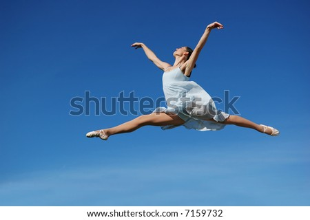 Ballerina performing a jump on a sunny day