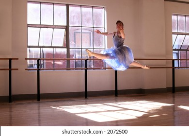 A stock photo of a ballerina performing a grand jete'.