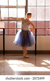 A stock photo of a ballerina practicing in a studio.