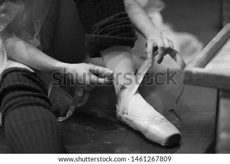 Ballerina sits on the floor in the theater's rehearsal hall and puts on pointe shoes