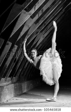 Ballerina wearing white tutu standing on one leg  in hangar